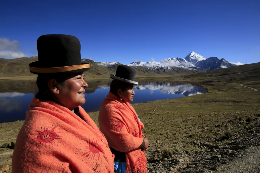 Aymara indigenous women Lidia Huayllas, 48, (L) and Dora Magueno, 50, stand near Milluni lake, with the Huayna Potosi mountain in the background, Bolivia.