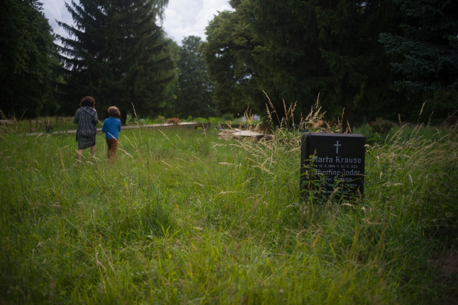 """A mother and son from the neighborhood enter a community garden called """"Die Gartnerei"""" that has sprung up in the retired section of the cemetery of the Jerusalem Church in the Berlin district of Neukolln. The garden grew up as a project of a non-profit ma"""