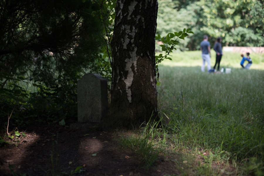 A young family plays in Berlin's Leise Park, just yards way from this headstone. Though many of the headstones and remains have been removed from the park, some remain.