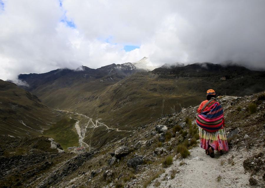 An Aymara indigenous woman walks on the Huayna Potosi mountain.