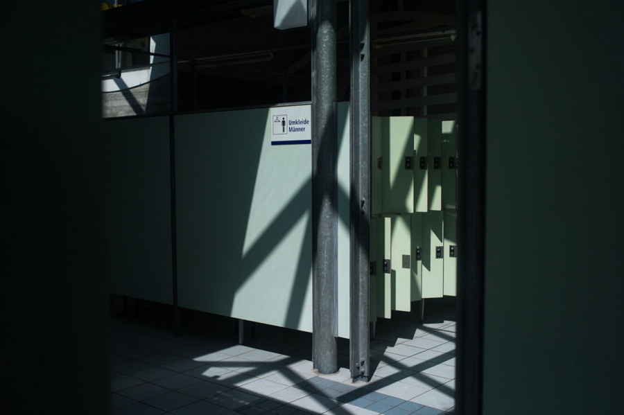 """The men's changing room lit by morning sunlight at the Sommerbad Neukolln. Last season, the biggest challenge for the project """"Bleibt Cool am Pool"""" started here. Many recently-arrived male refugees began arriving to swim wearing only cotton underwear, som"""