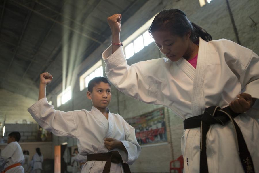 A young black belt leads Rai through a kata at the karate dojo where she trains daily in Kathmandu.