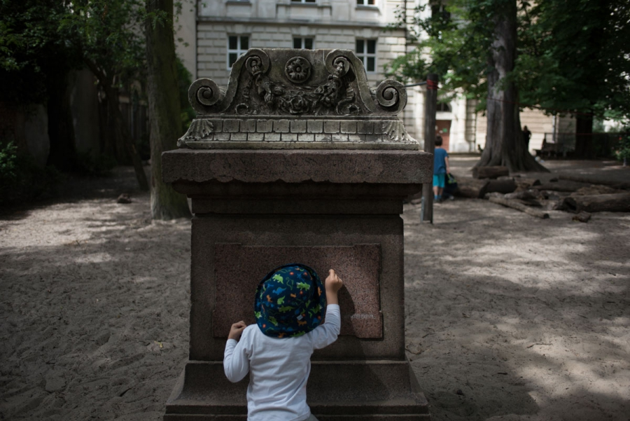 A pupil of the Sophienkirche day-care makes marks on a gravestone in the center's playground.
