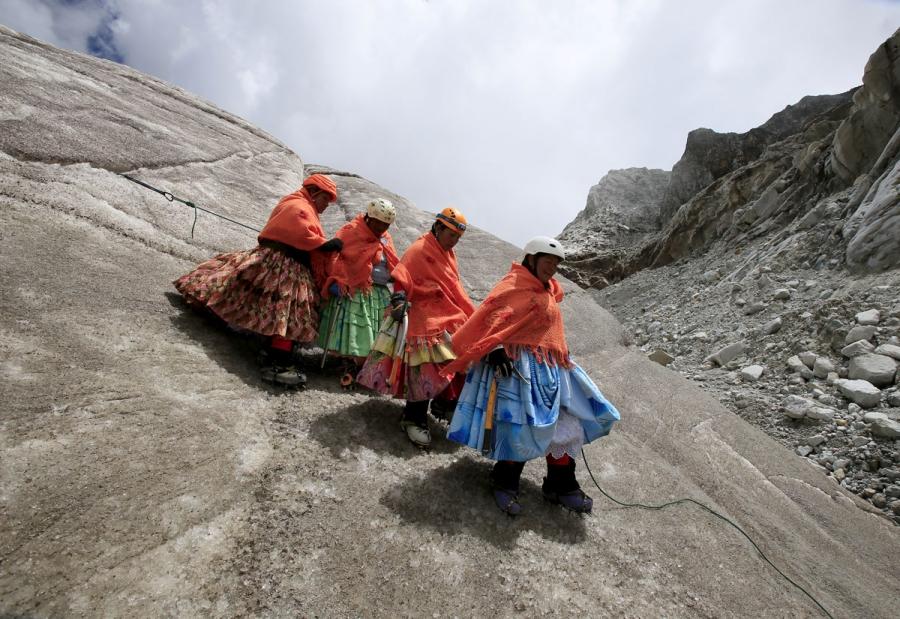 Aymara indigenous women practice descending on a glacier at the Huayna Potosi mountain.