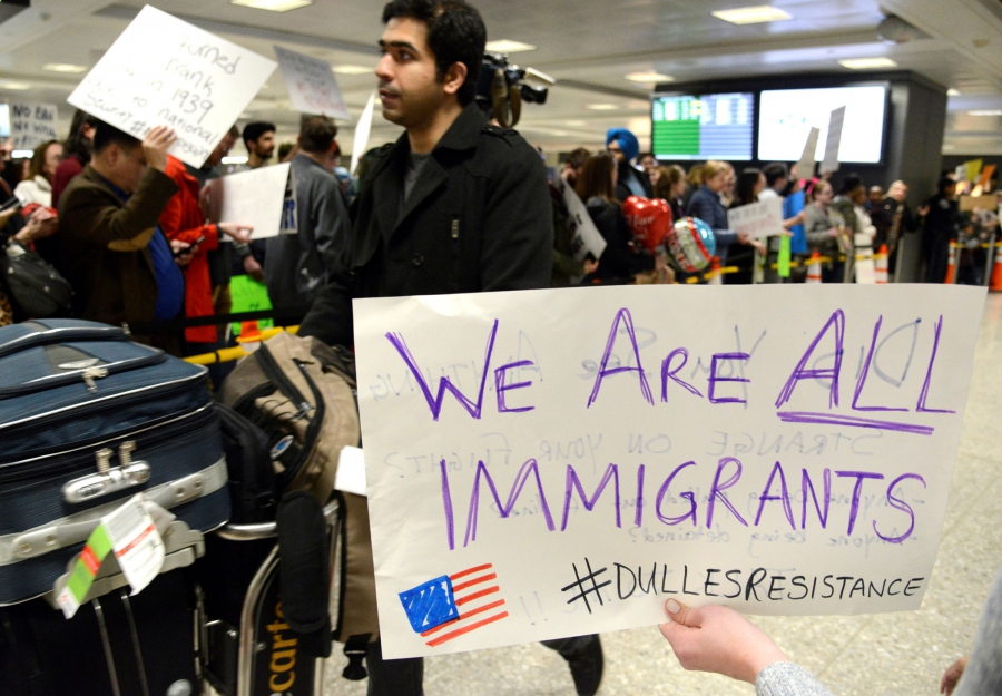 Dozens of pro-immigration demonstrators cheer and hold signs as international passengers arrive at Dulles International Airport.