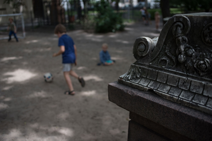 Pupils of the Sophienkirche day-care play soccer near a headstone in the center's playground. On this afternoon, the headstone also serves as a boundary line for the game.