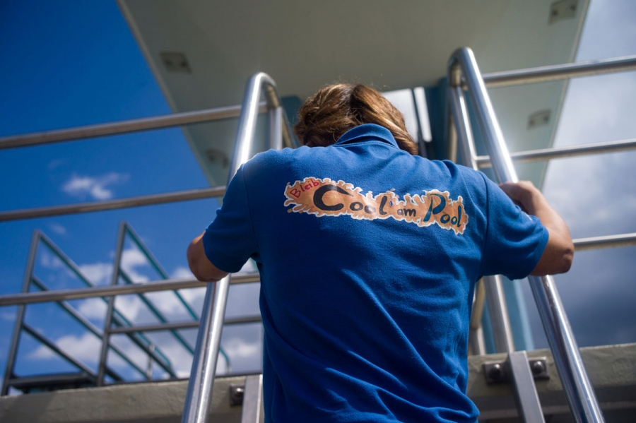 Social worker Nurcan Civelek climbs up to the diving platform at Sommerbad Neukolln in her work uniform. She says she enjoys her work, especially working with young people.