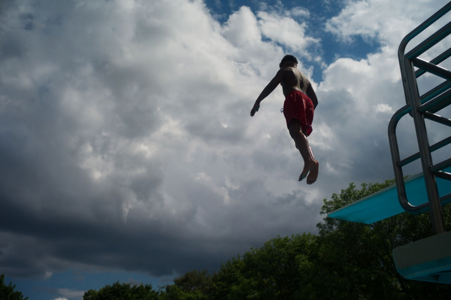 A young pool guest jumps from the diving platform of the Sommerbad Neukolln as storm clouds roll in. The director of the pool says that despite the forecasts, they are expecting a peaceful summer at the facility.