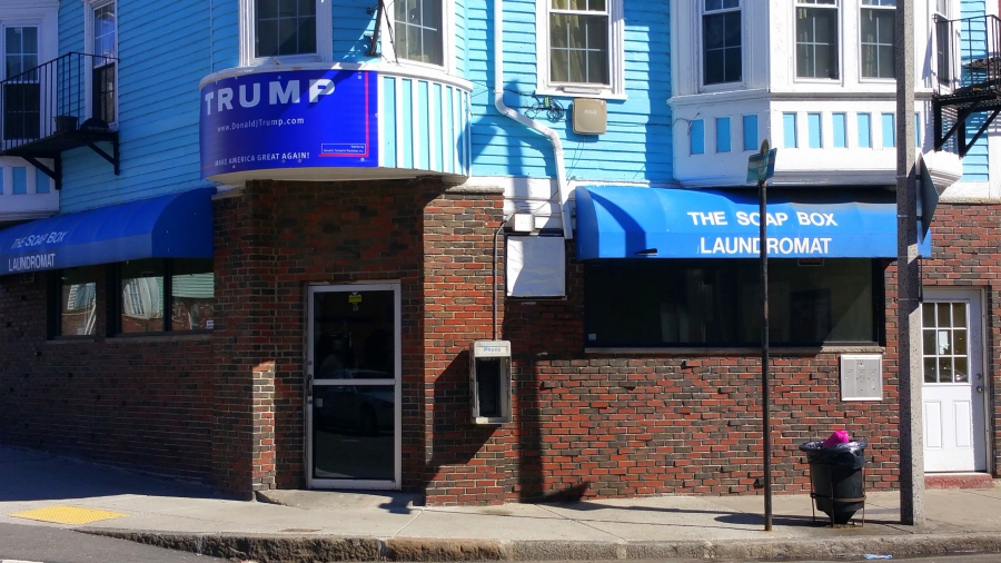 <p>A pro-Trump sign hangs above The Soap Box Laundromat in East Boston.(Phillip Martin/WGBH)</p>