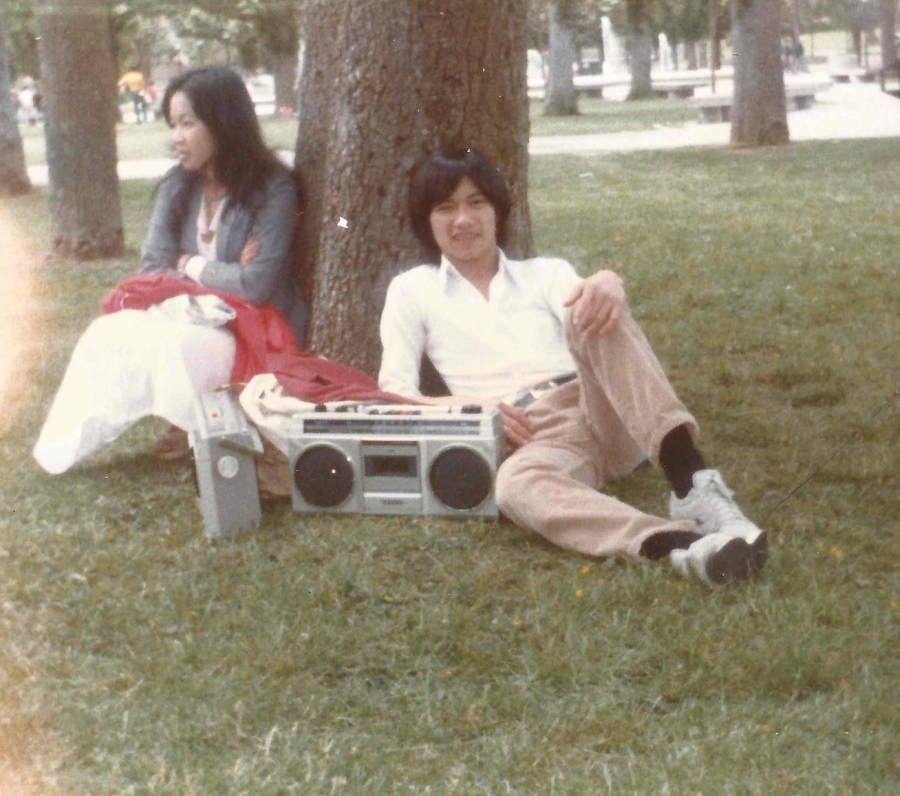 The author lounges by a tree next to his boombox, and an unidentified woman