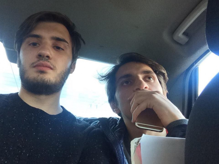 Felix Glyukman and Islam Abdullabeckov being escorted in police vehicle after being detained by Russian authorities.