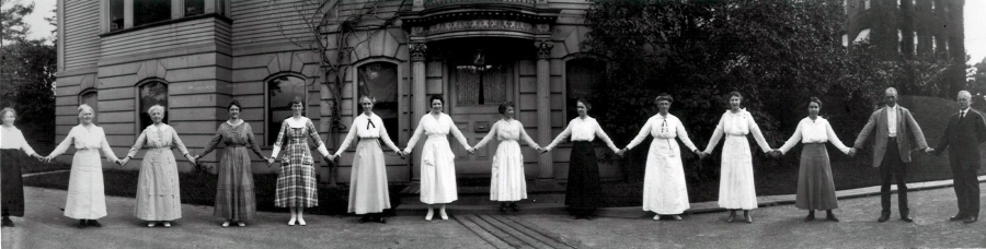 "A dozen women hold hands in front of a building on the Harvard campus in 1918. They are all women ""computers"" working in the Harvard College Observatory. At the far right of the image is Edward Pickering, the head of the Observatory who hired them all."
