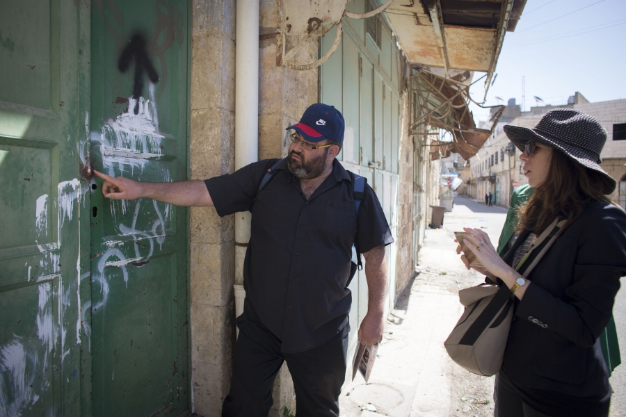 """Yehuda Shaul of """"Breaking the Silence"""" shows author Rachel Kushner graffiti in the West Bank city of Hebron that reads """"Death to Arabs."""""""