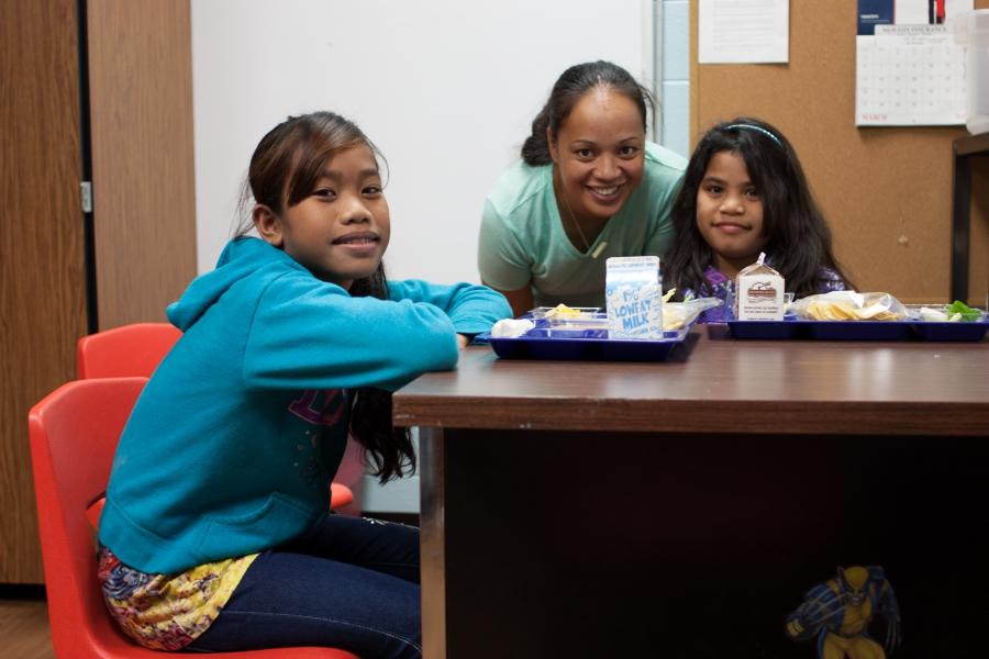 Two young girls and woman look at the camera with lunch trays in front of them