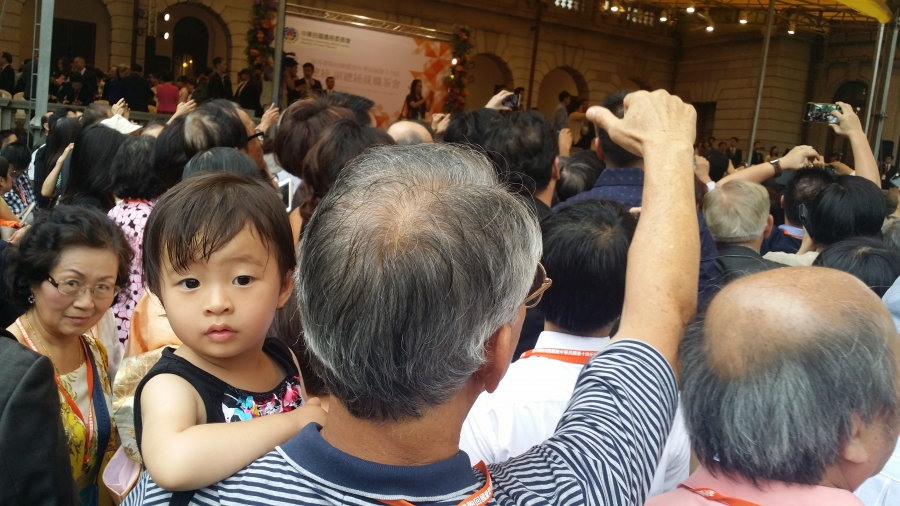 Young girl carried by man faces camera while man cheers in crowd