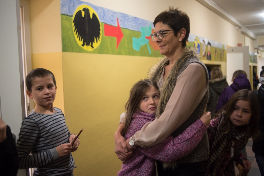 Gabriela Thomas, director of the elementary school in Golzow gives a student a hug between classes in the main hallway. Thomas says that the children of the refugee families are already fitting into her school very well.