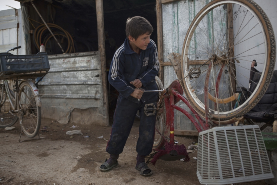 Ebraham Alatmia, 11, a Syrian refugee from Daraa, fixed a bicycle in a makeshift bike shop where he works in the main marketplace nicknamed Champs-Elysée.