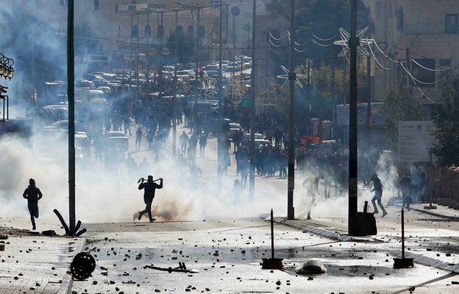 Palestinian protesters run for cover from tear gas fired by Israeli troops during clashes at a protest, in the West Bank city of Bethlehem Dec. 7, 2017.