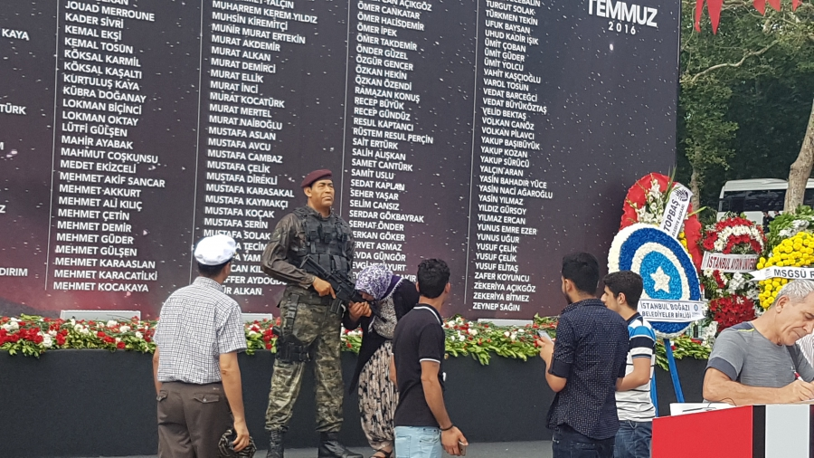 A woman kisses the hand of a plastic replica soldier, in front of a list of people killed during the coup attempt, in Istanbul's Taksim Square.
