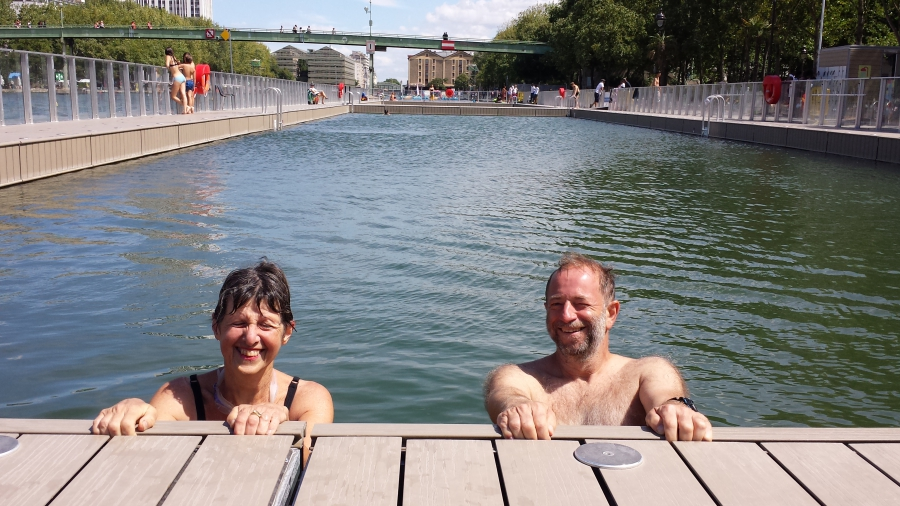 A man and woman beam up at the camera as they hold onto the edge of the pool.