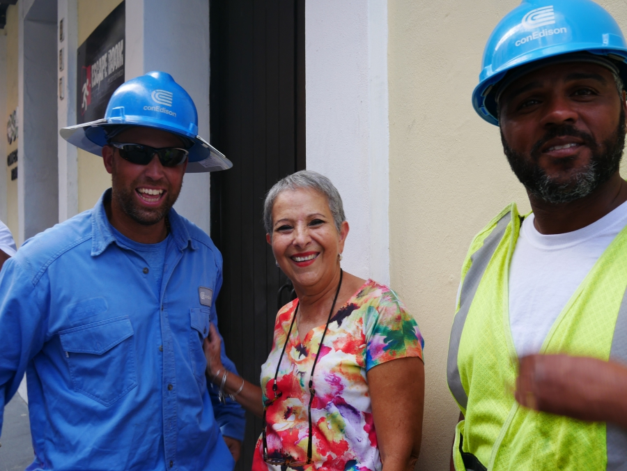 "Marisol Maldonado poses with Con Ed linemen minutes after they restored electricity to the travel agency where she works in Old San Juan. ""These are heroes!"" she said."