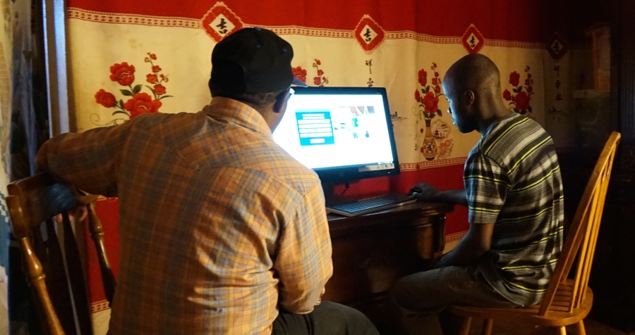 Man sits at computer facing screen with another man sitting next to him looking on