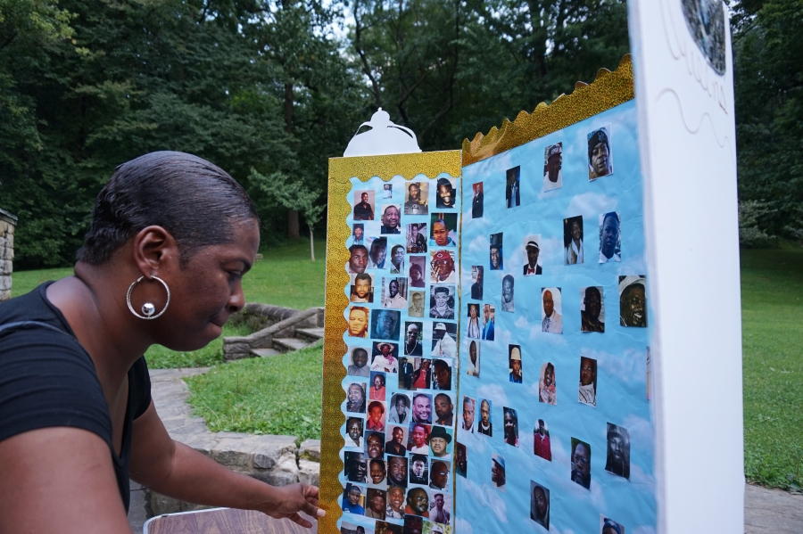 Catrina Herring looks at a poster board covered in photographs of residents of Northview Heights lost to gun violence.