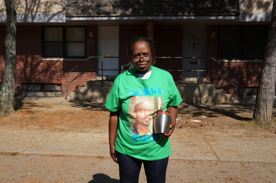 Keisha Allen stands outside her apartment holding an urn containing her son's remains.