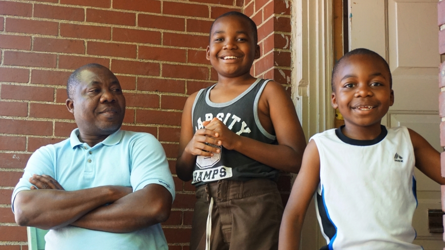 Man with folded arms looks at two smiling young boys, in front of door