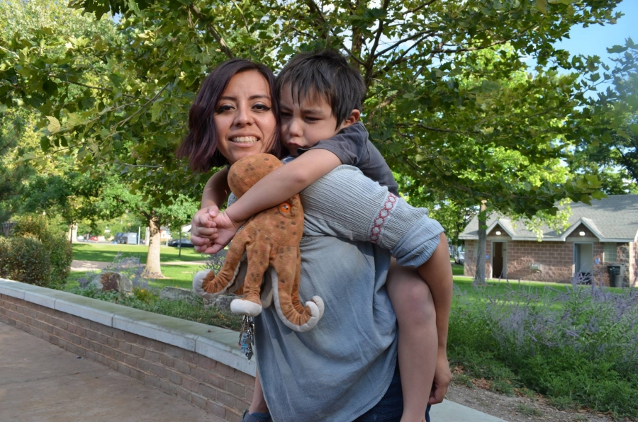 Woman outdoors with child holding teddy bear on her back, she is smiling
