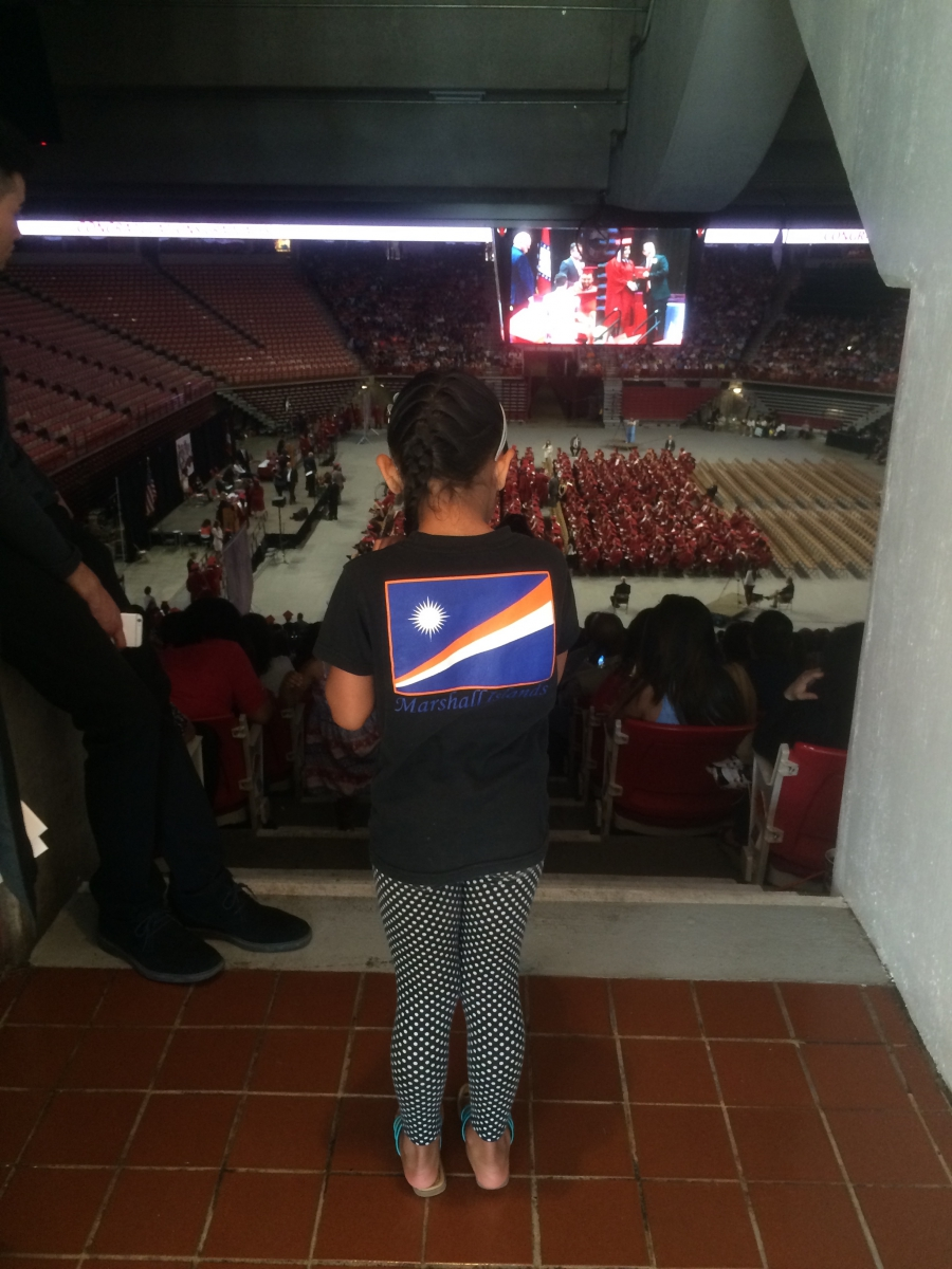 A young girl looks at graduation ceremony from above, in arena