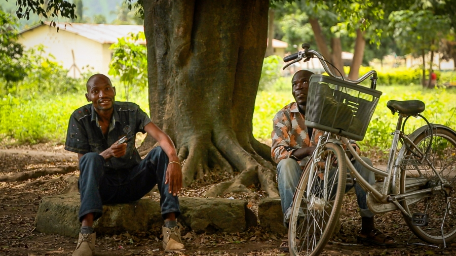 Two men rest under a group of trees that's home to hundreds of fruit bats in the town of Kilombero. The trees are a favorite shaded spot for people traveling the hot and busy stretch of road along Tanzania's Kilombero Valley, leading to concerns about inf