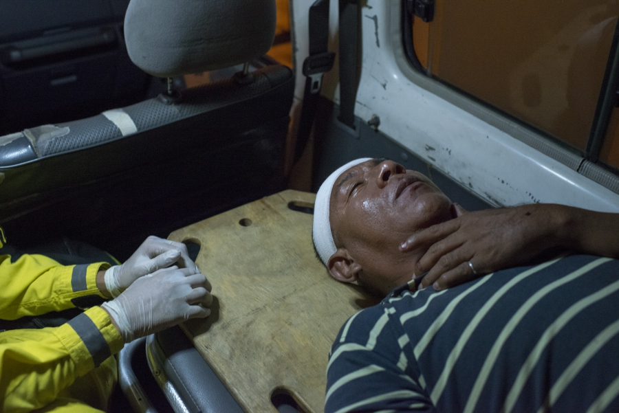 Edwin Alberto Orantes gives first aid to a victim who was robbed while he is being transported to a hospital.