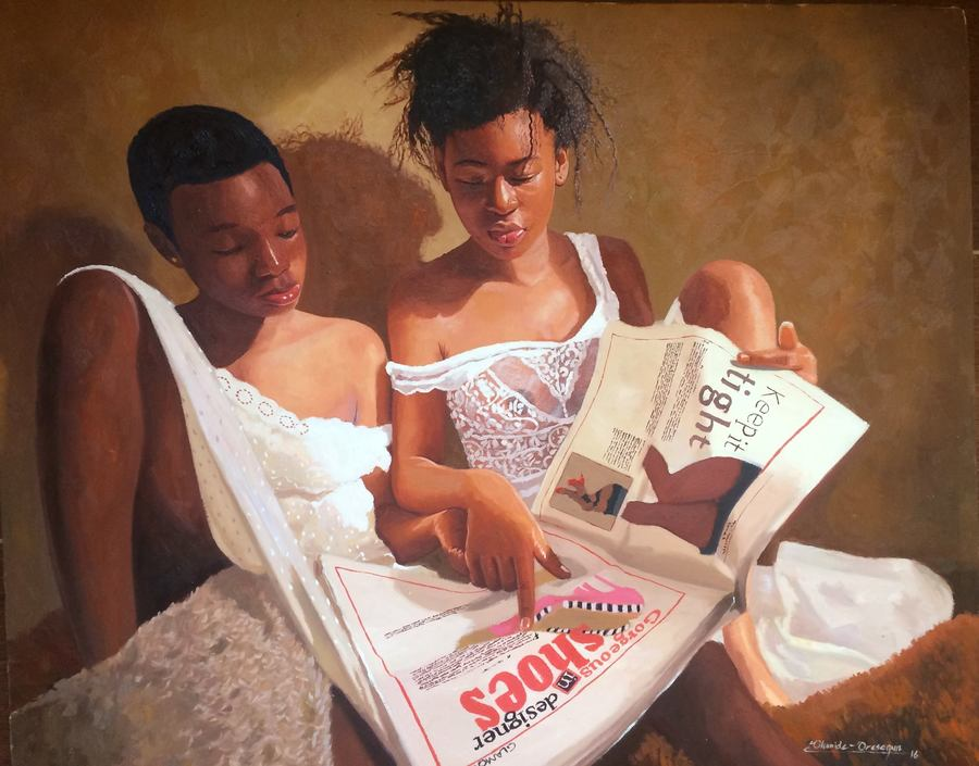 Two girls reading a newspaper.