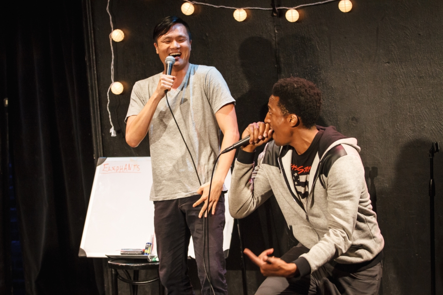 Two performers with microphones are laughing and performing their rap.
