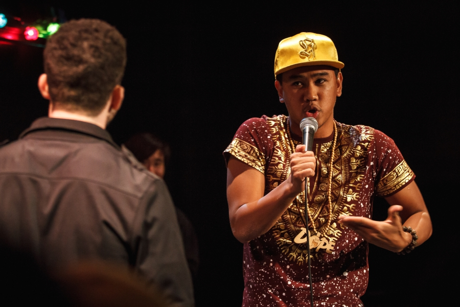 A man is in a face-to-face battle with another performer. He is holding a mic with one hand and gesturing with another.