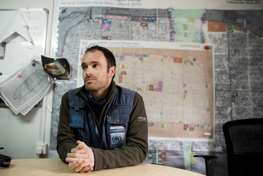 Gavin White, UNHCR External Relations Officer, sits in front of maps of the camp's sprawl at the UN refugee agency's Zaatari camp headquarters.