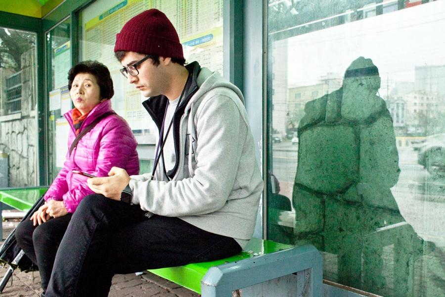 Ahmed Lababidi checks his phone waiting for the bus.