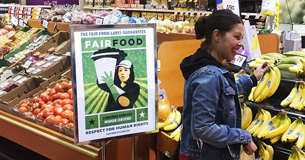 A Fair Food Program sign next to tomatoes for sale in a supermarket produce section.
