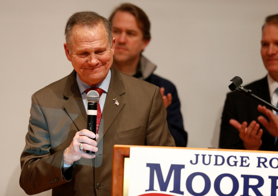 Republican US Senate candidate Roy Moore stands with microphone in hand behind a placard of his campaign poster.