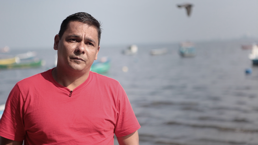 43-year-old fisherman-turned-activist Sandy Anderson stands on the shore of Brazil's Guarabana Bay, just outside Rio de Janeiro. Anderson says he's nearly been killed twice fighting to save this bay from polluters, and now lives in hiding.