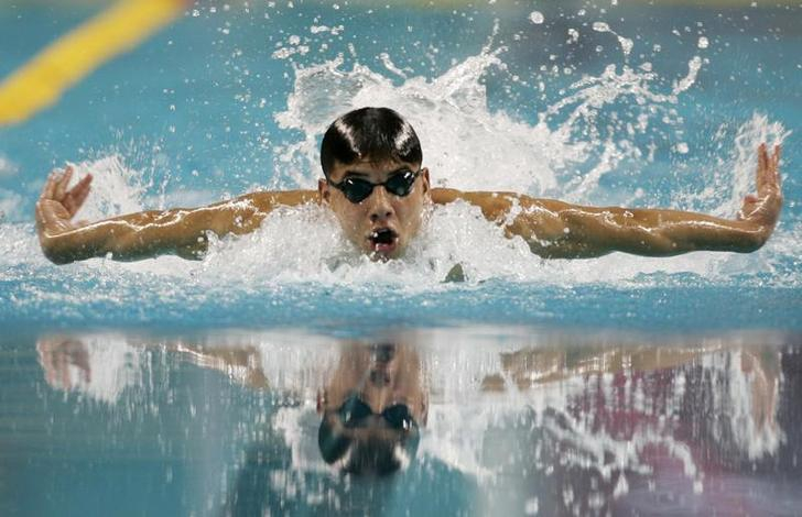 Syrian swimmer Rami Anis, wearing goggles but no swimmer's cap, emerges above the water during a butterfly stroke