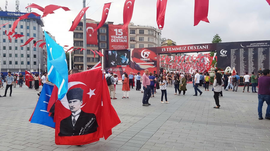 A vendor holding a Mustafa Kemal Atatürk flag walks outside the July 15 memorial area set up in Istanbul's Taksim Square.