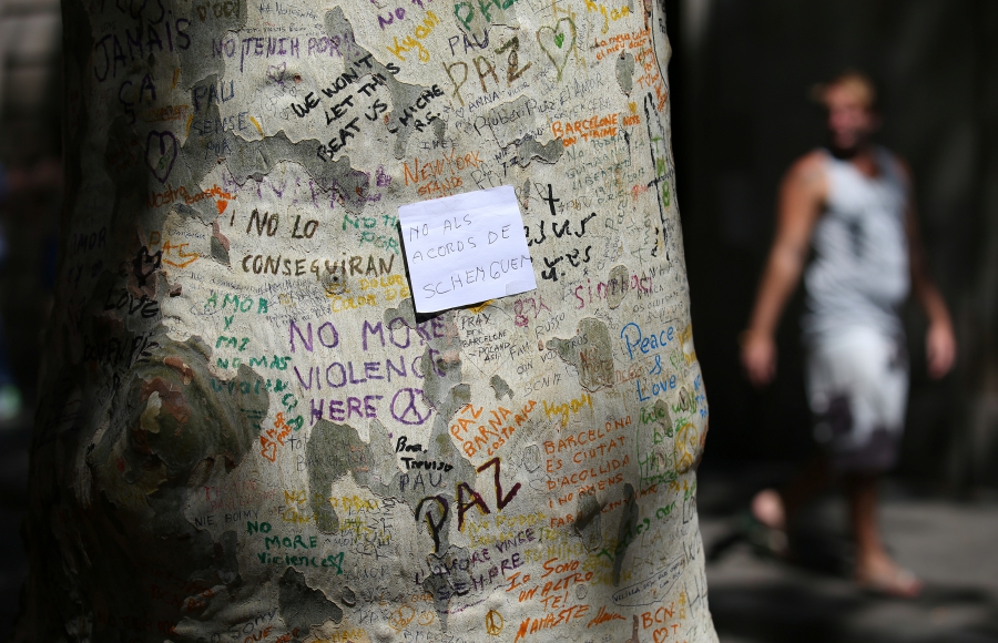 "A paper with the sentence ""Not to the schengen agreements"" written on it is seen on a tree trunk at an impromptu memorial at the site where a van crashed into pedestrians at Las Ramblas in Barcelona."