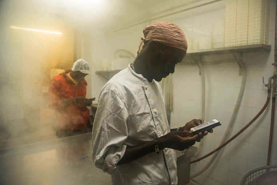 Cheikh Diop in the foreground and Ismael pass time as they wait for the recycled jars to sterilize with steam.  Making yogurt can take up to 10 hours.