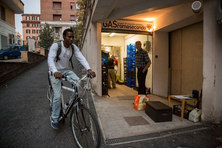 Barikama co-founder Seydou Baldeh from Gambia delivers yogurt on a bike to an ethical buyers group in Rome.  They keep the yogurt cool in black styrofoam boxes that empty out fast.