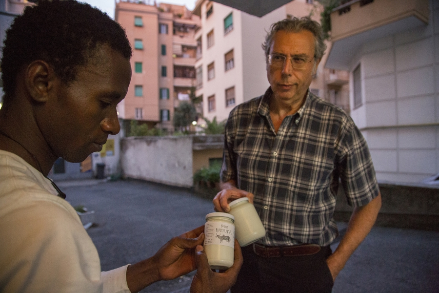 Seydou places a Barikama label on a jar of yogurt before selling it.  The company logo features a typical African cow with a hump.  It's become an image that many Roman circles admire and expect.