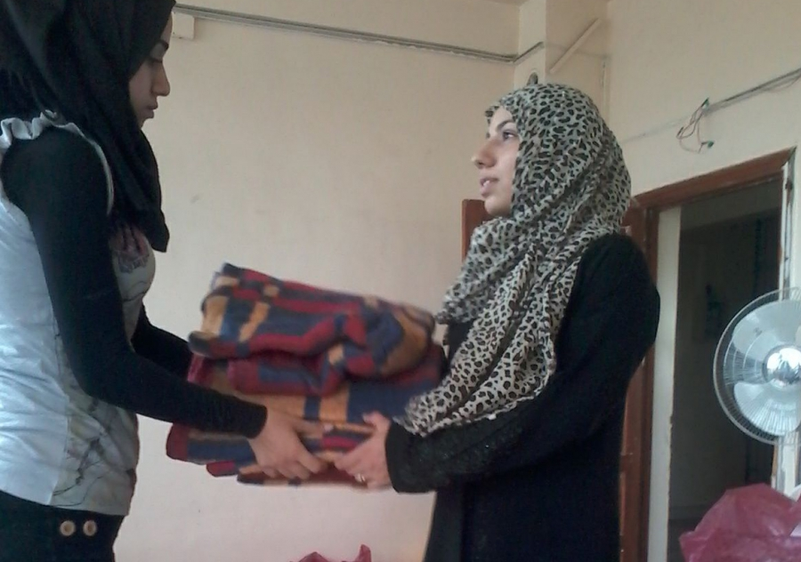 A Questscope volunteer gives a blanket to a woman who fled her home near the Syrian city of Hama after fighting there earlier this year.