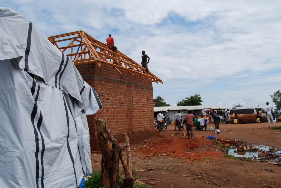 Men build a brick shop near the entrace of Bidi Bidi. Most of the buildings are temporary, but slowly permanent structures are rising up.