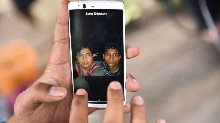 Fardan Rezeky shows pictures on his phone of friends he's made in the Rohingya and Bangladeshi refugee camp in Bayeun, on July 19, 2015. Rezeky was there in May when the refugees arrived. He felt a call to help them, as many other countries helped Aceh af